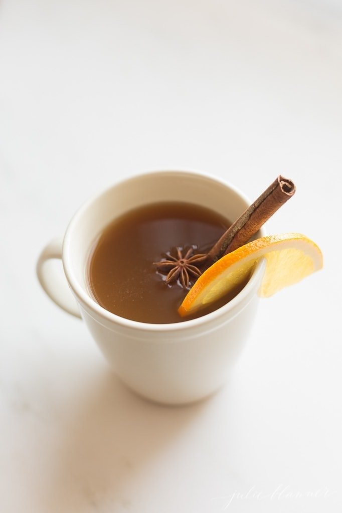 spiked apple cider in a white mug with cinnamon, star anise, and orange slice
