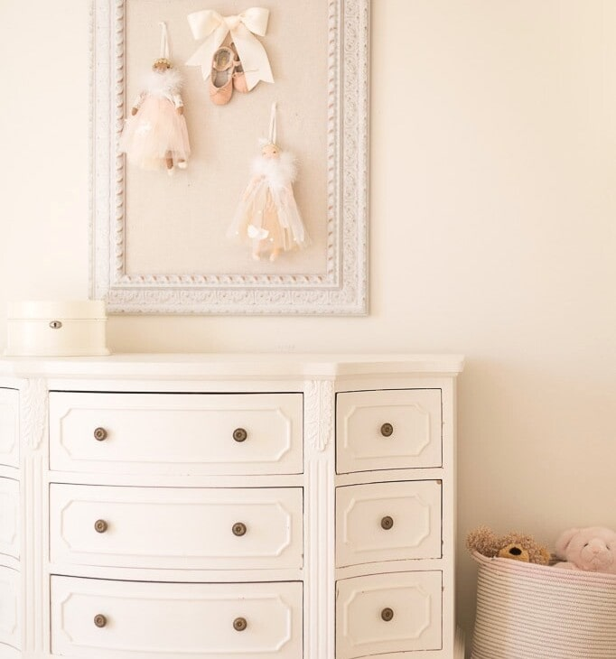 cream bedroom with pin board dresser and basket of stuffed animals