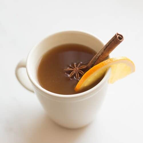 spiked apple cider in cream mug with orange slice cinnamon stick and star of anise