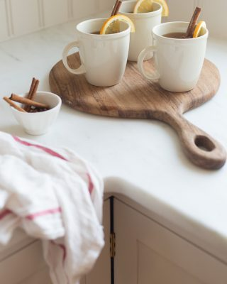 spiked apple cider in white mugs on a wooden board with cinnamon sticks
