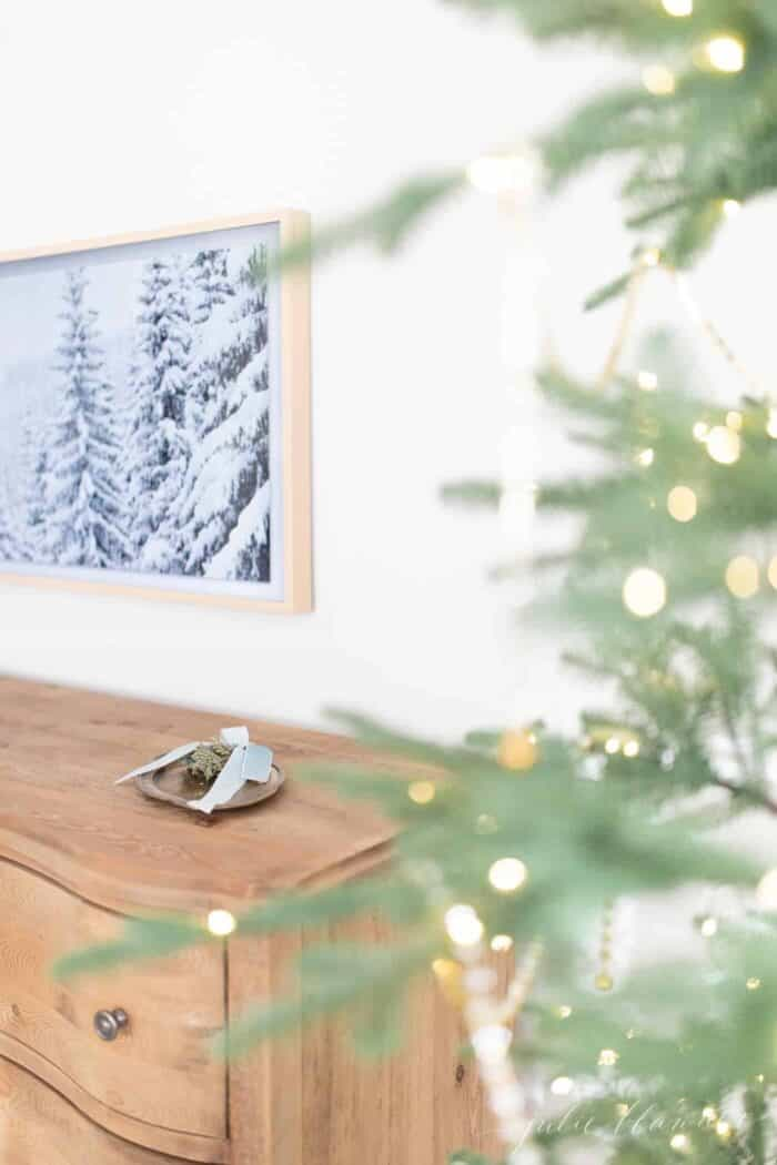 A Samsung art tv on the wall of a bedroom with a winter scene displayed, Christmas tree in foreground.