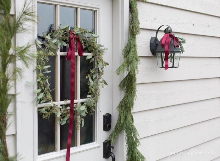 pine garland and red ribbon christmas door decorations