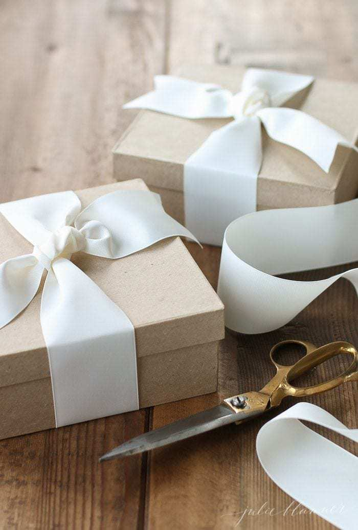 Wooden surface with kraft paper brown boxes, white ribbon and scissors packaging homemade Christmas gifts.