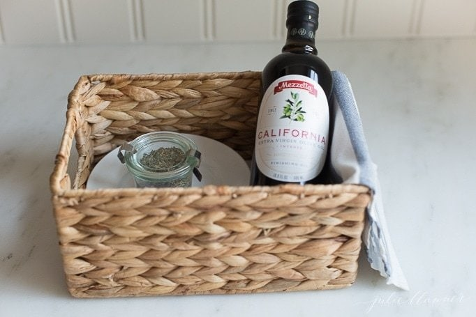 A basket with the herb mix and a bottle of olive oil