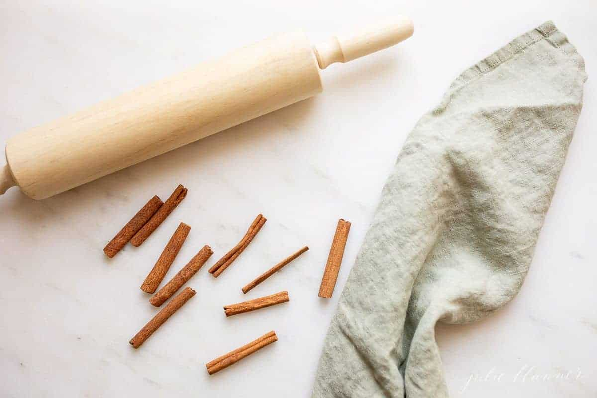 A wooden rolling pin on a marble surface, crushed cinnamon sticks and a linen towel.