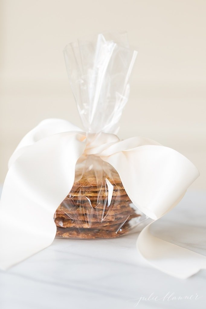 stack of oatmeal lace cookies wrapped in cellophane with ribbon on a marble surface