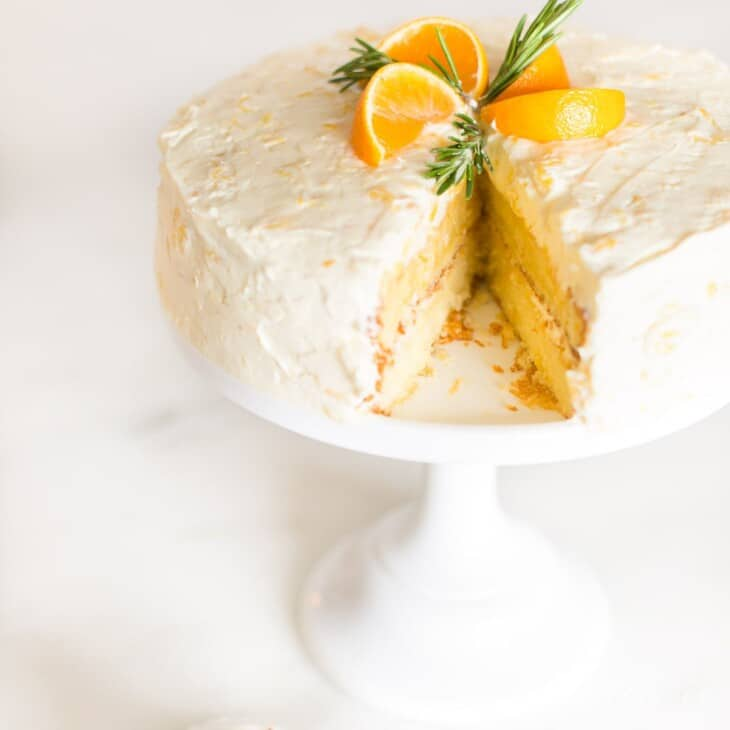 A round mandarin orange cake with a slice removed, placed on a white cake pedestal.