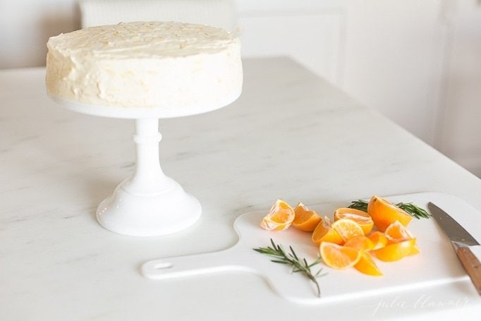 a mandarin orange cake on a white pedestal, slices of oranges and rosemary on a cutting board to the side.