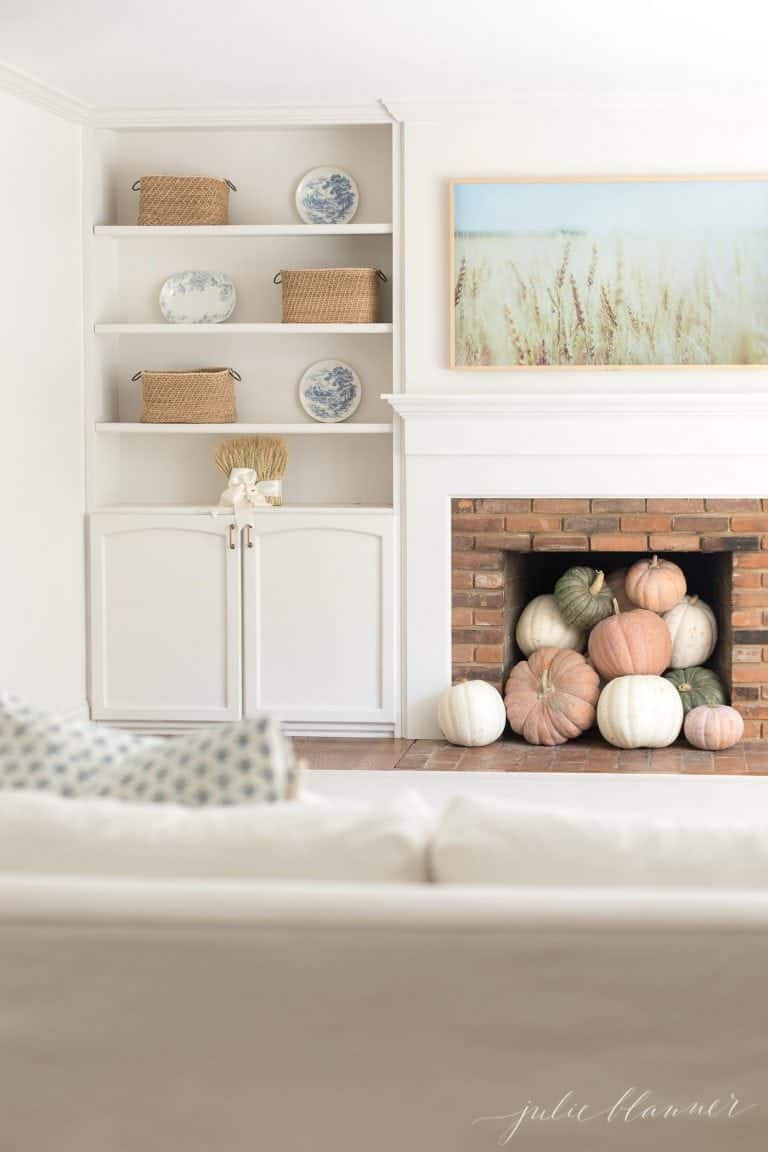 A white living room with a Samsung Frame TV that looks like art over the mantel, pumpkins inside fireplace and a fall image on the tv.