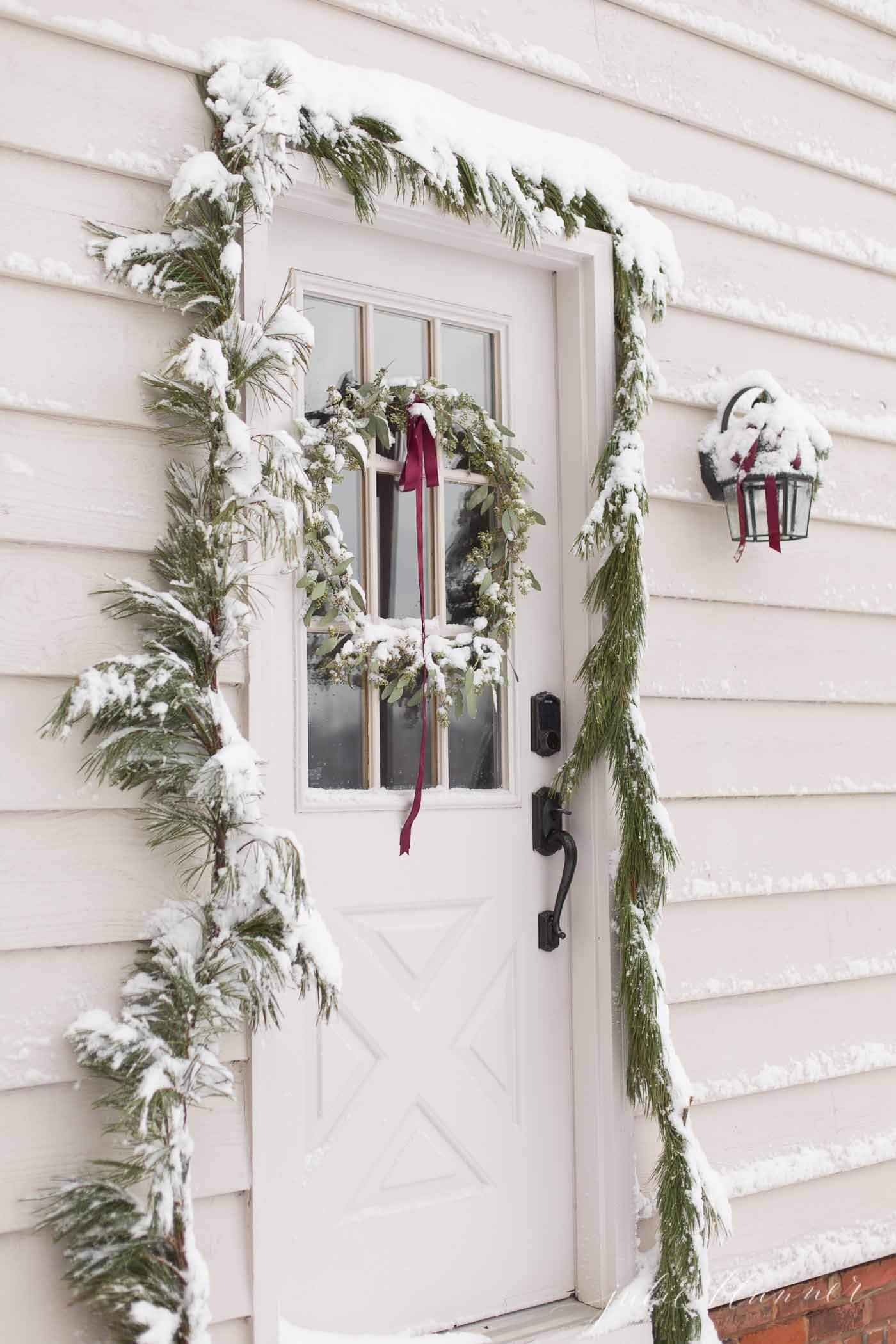 christmas door with a DIY wreath and garland covered in snow