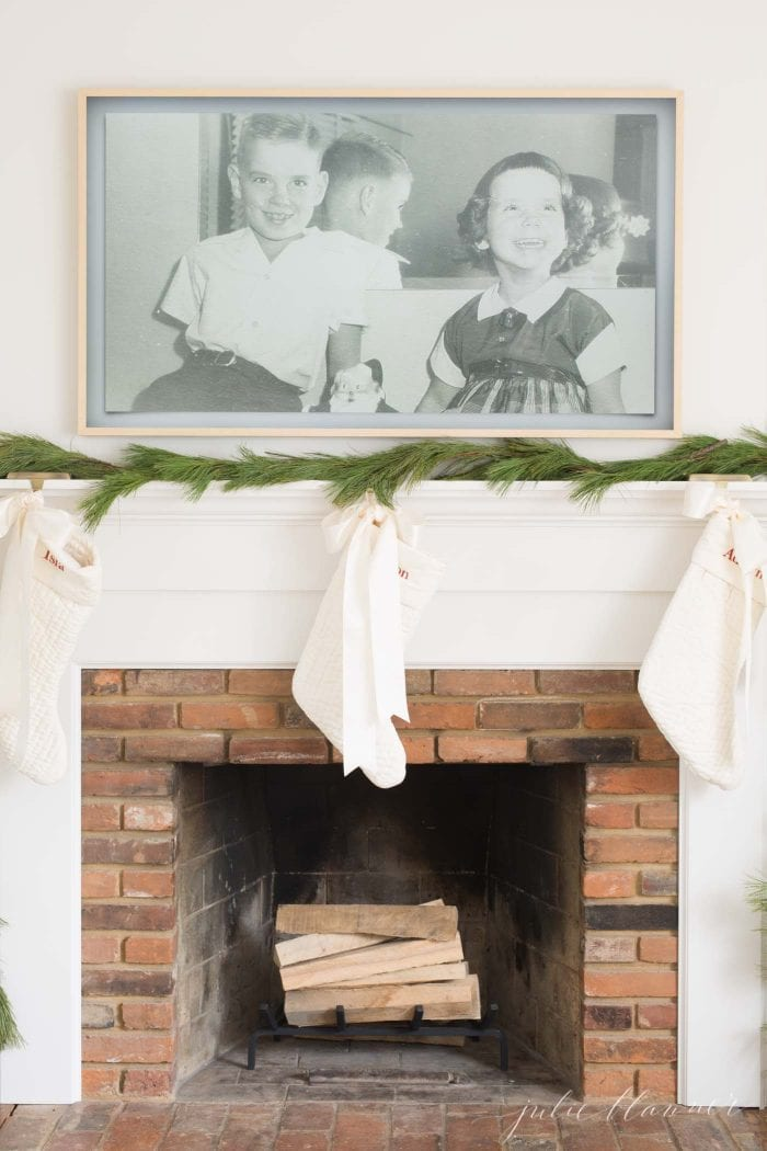 tv over fireplace with garland and stockings