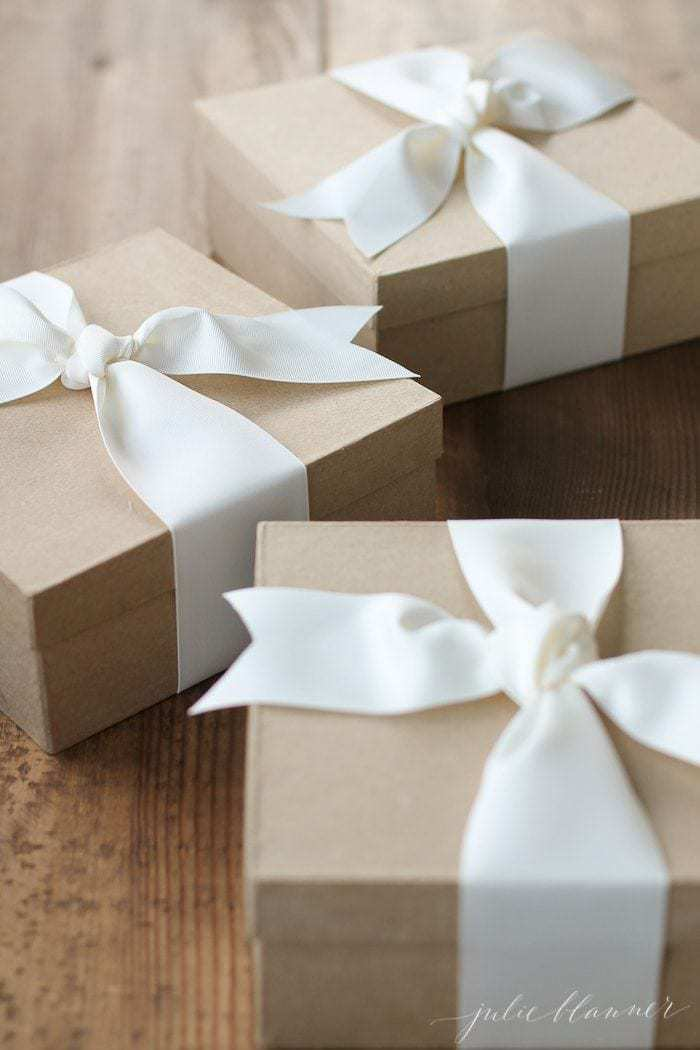 Wooden surface with kraft paper brown boxes, white ribbon packaging homemade Christmas gifts.