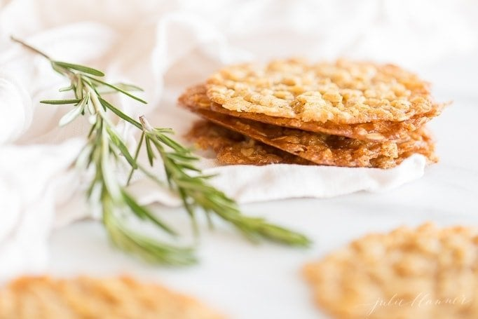 oatmeal lace cookies on linen napkin next to rosemary garnish