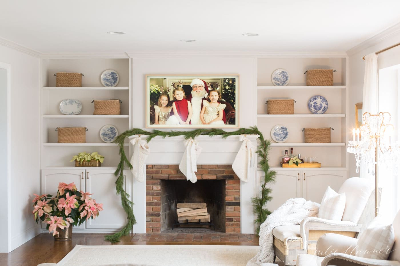 A picture frame tv on the wall over a traditional fireplace decorated for Christmas.