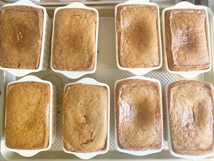 8 mini loaves of bread, baked in ceramic loaf pans, fallen in the center.