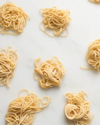 small swirls of spaghetti style egg noodles on a marble countertop. Homemade egg noodles in little serving sizes.