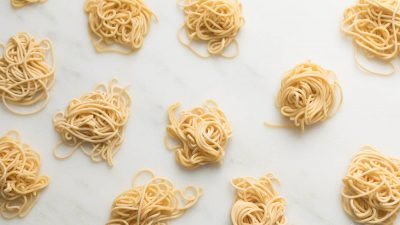small swirls of spaghetti style egg noodles on a marble countertop