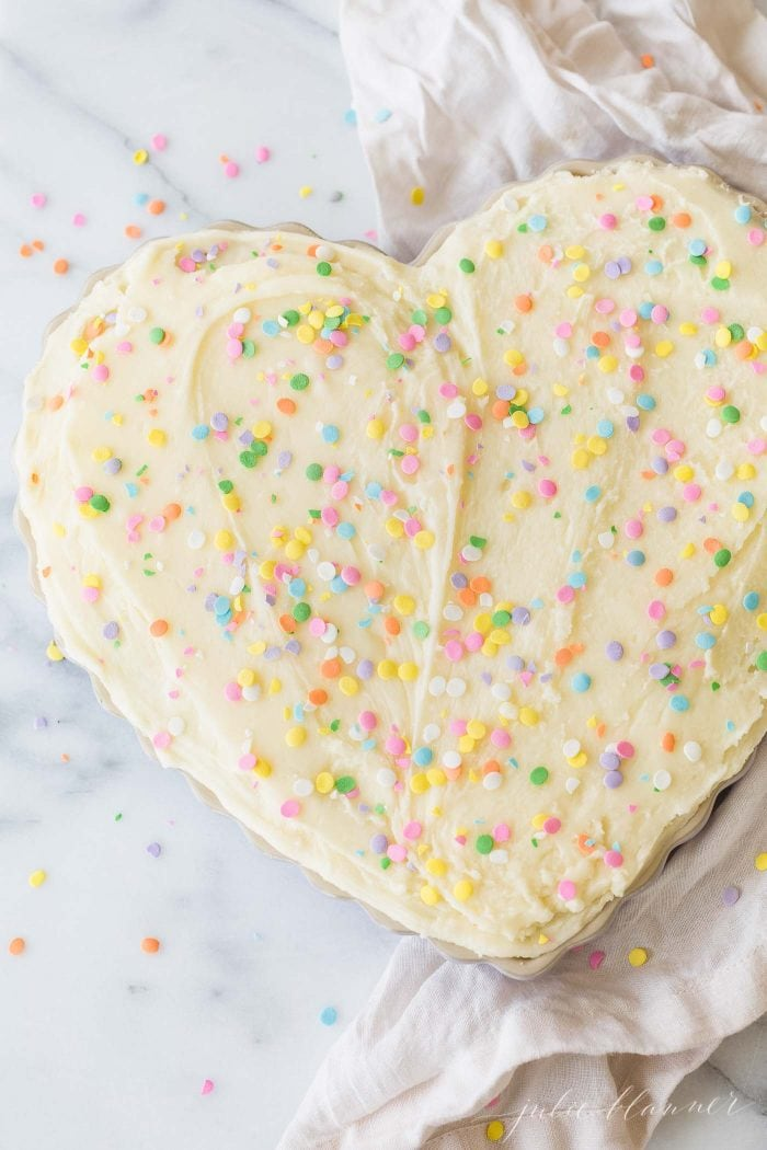 A heart shaped sugar cookie cake with frosting and sprinkles