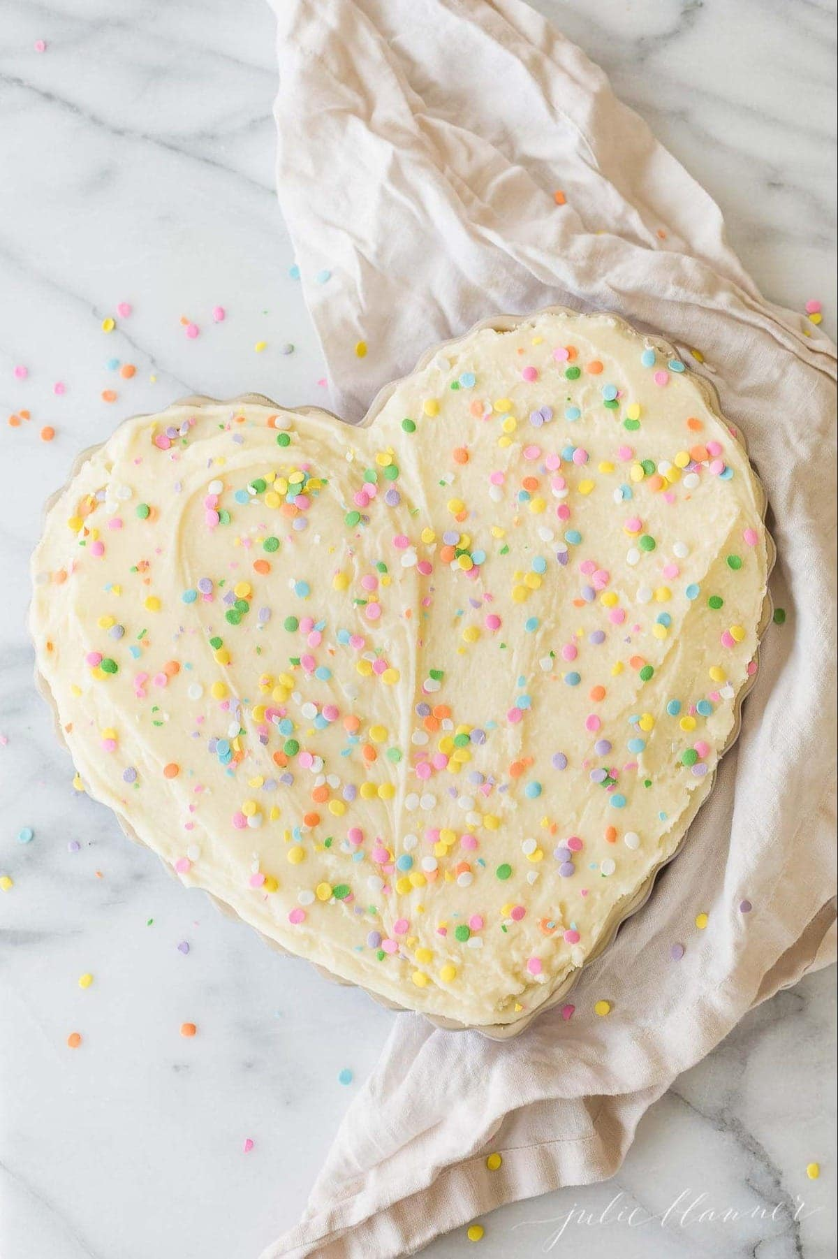A decorated heart shaped cake on a marble work surface