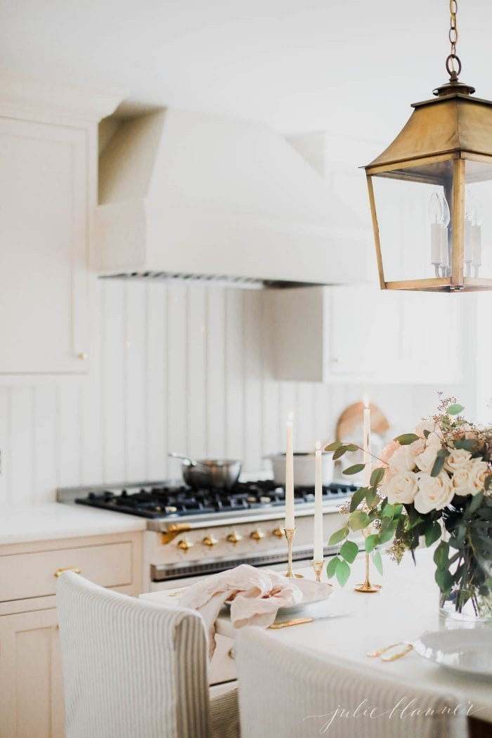 cream kitchen with brass lighting and lacanche range