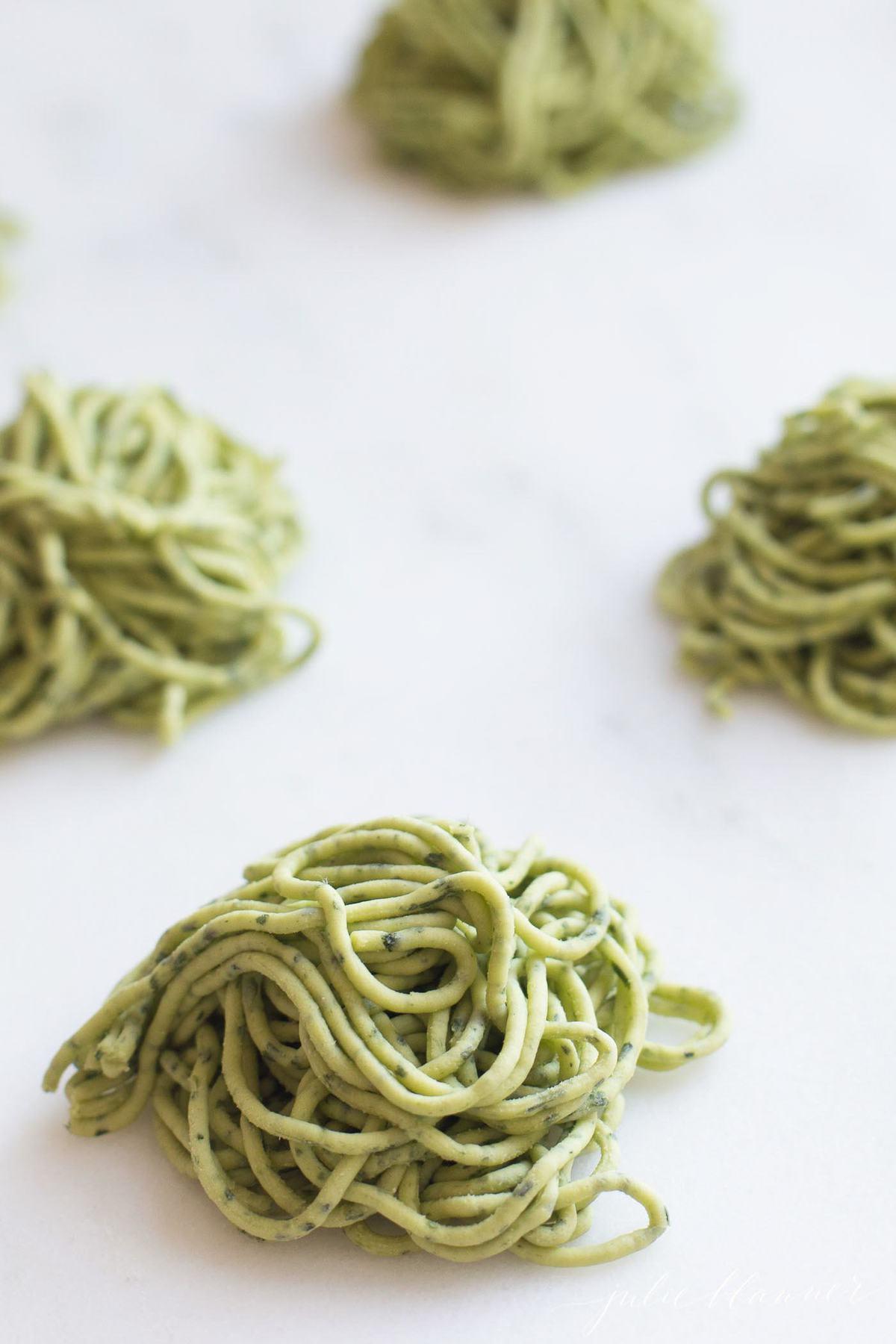 Uncooked arugula pasta in small piles
