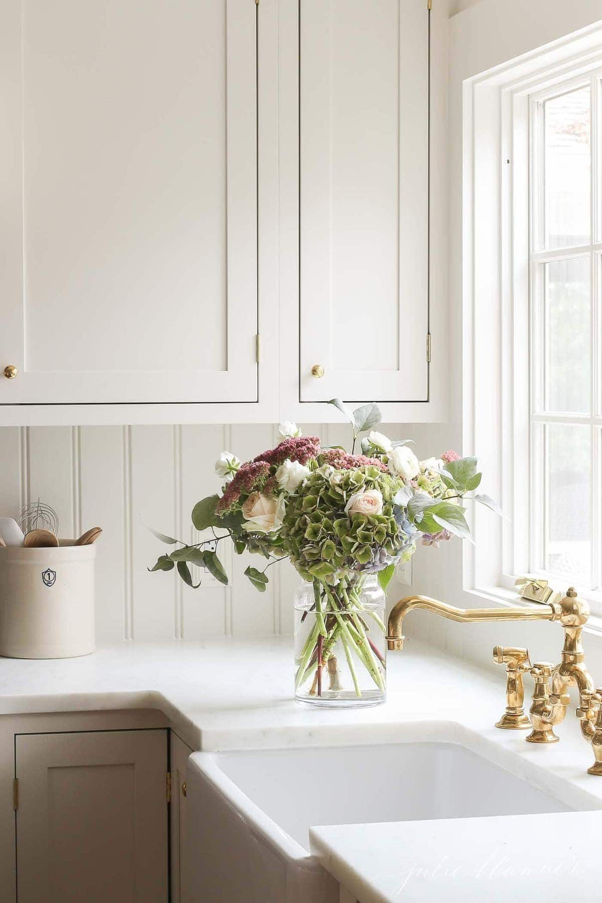 A bright and cozy home kitchen with white cabinets, brass faucet and a vase of flowers by the sink.