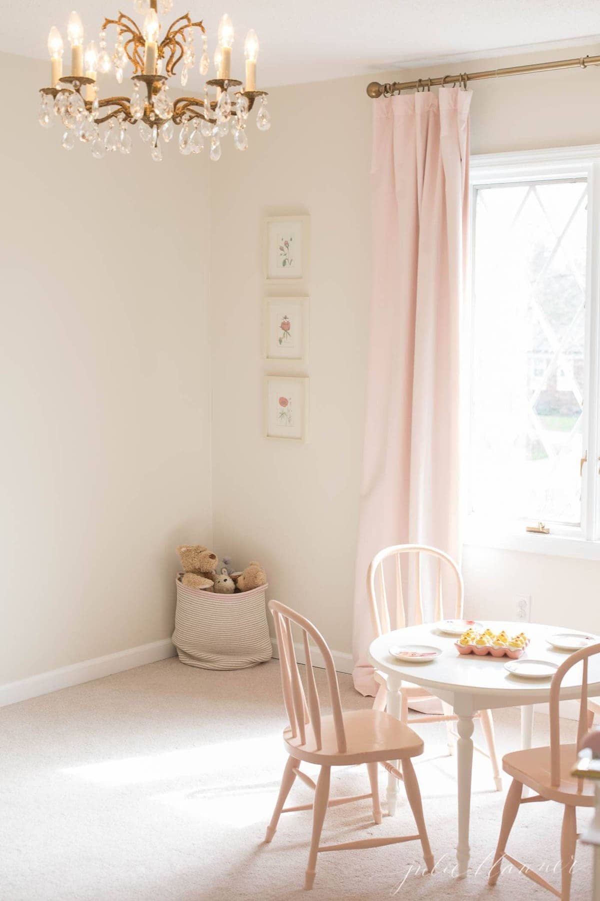 A little girl's room in a cozy home, featuring velvet drapes and a vintage chandelier.