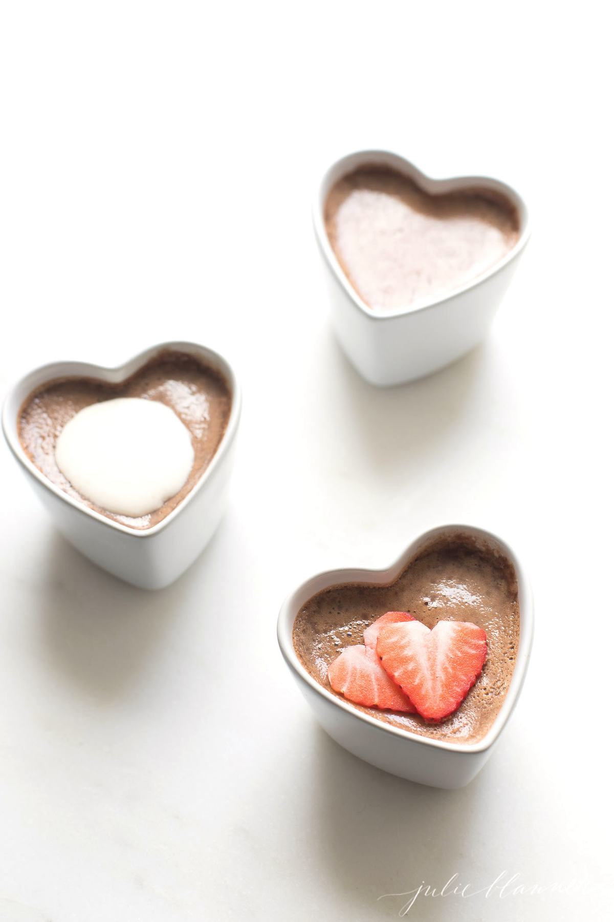 3 heart ramekins with chocolate pots de creme garnished with creme and strawberries