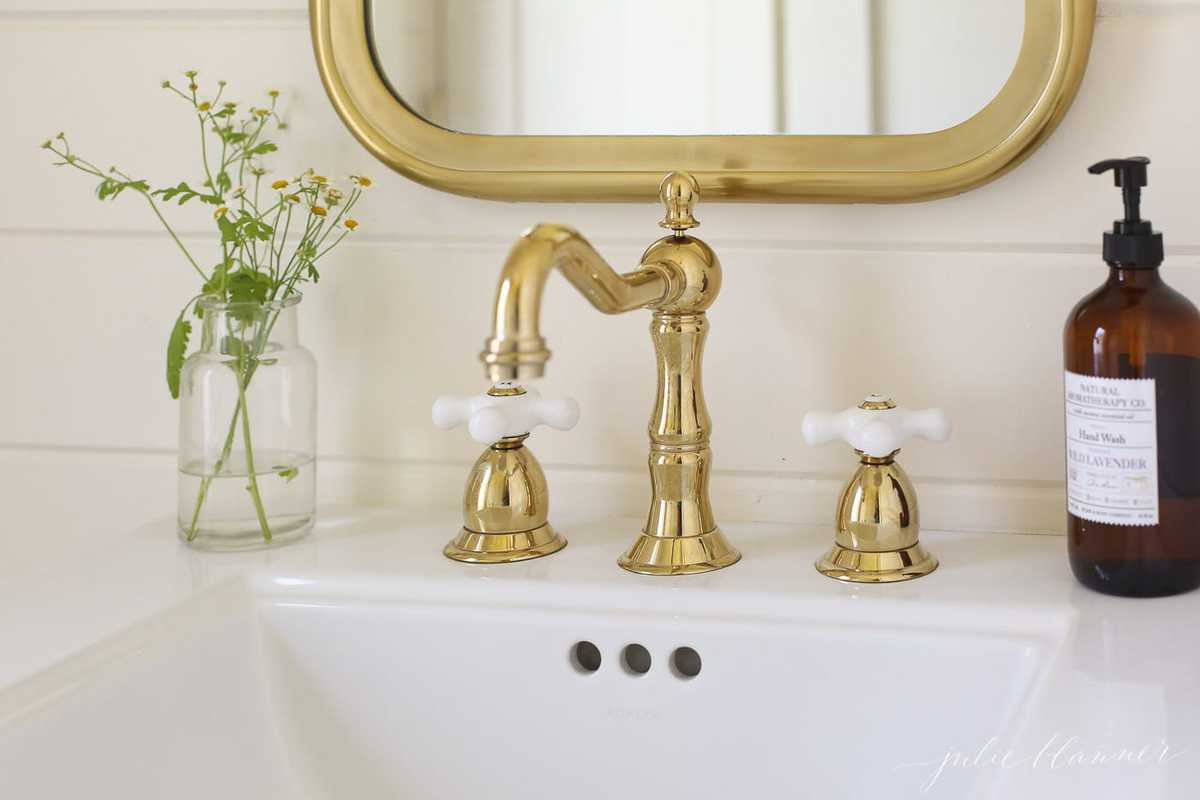 A white bathroom sink close-up shot, brass faucet and brass mirror above.