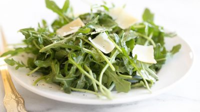 arugula salad recipe with parmesan shavings on white plate