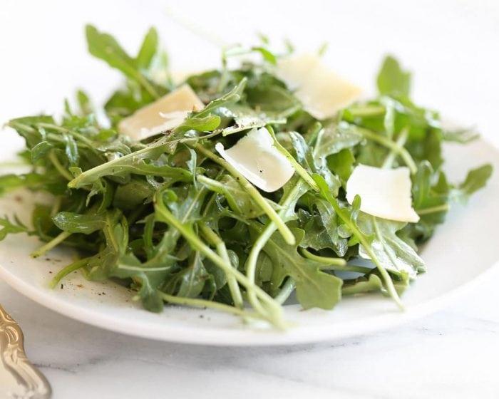 arugula salad recipe with parmesan shavings on white plate