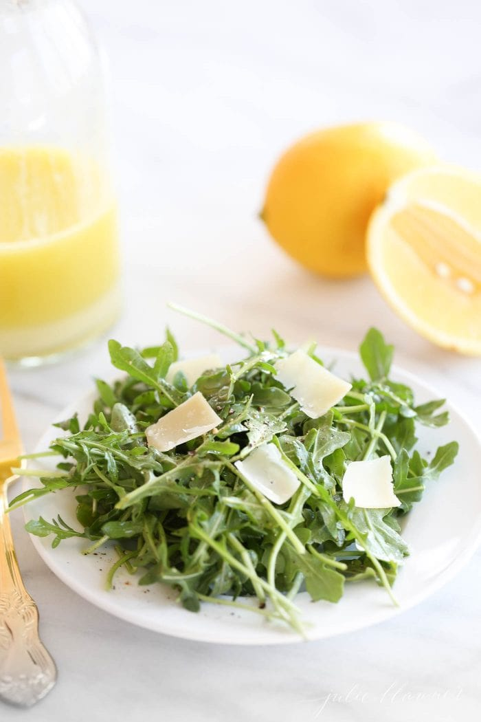 arugula salad recipe on white plate with parmesan and lemon vinaigrette