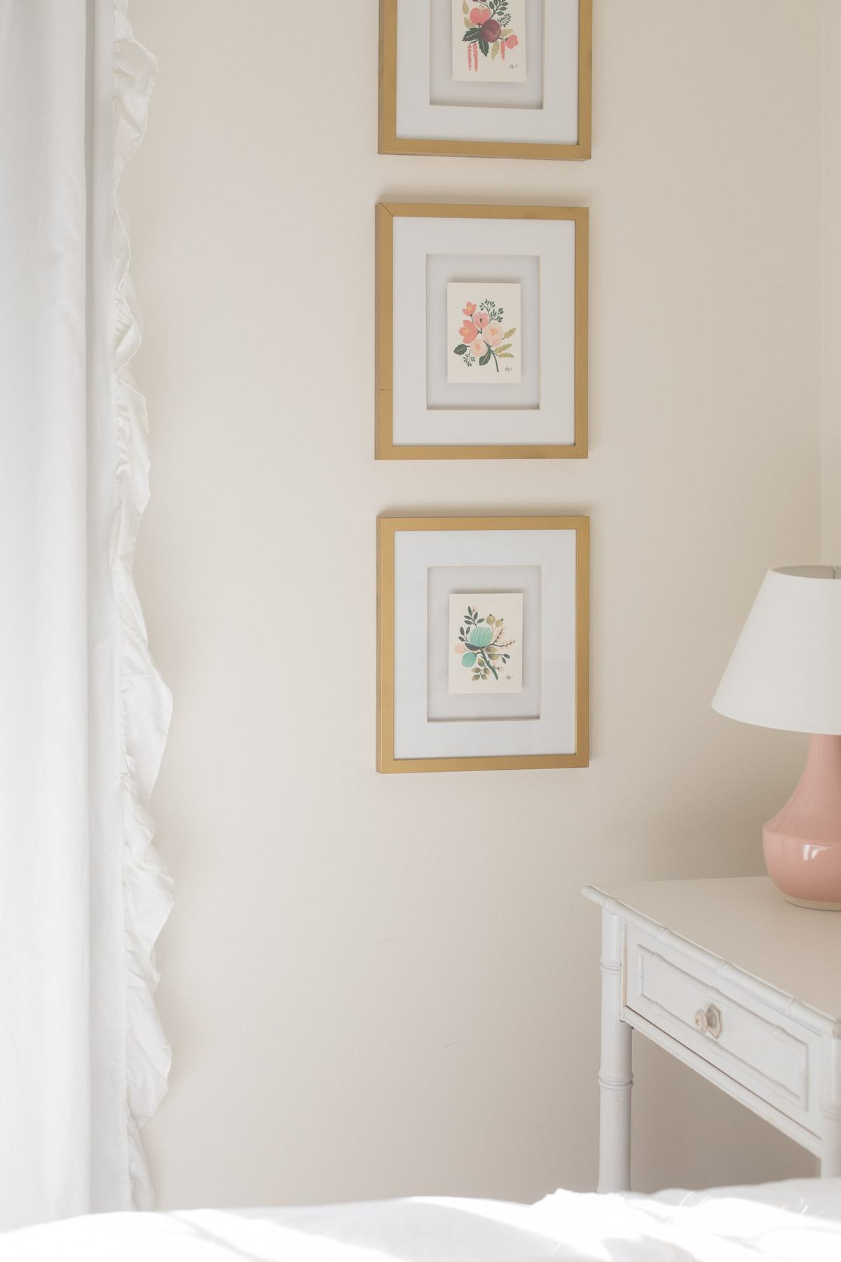 Gold framed art in a girl's white bedroom.