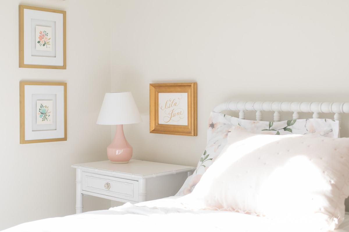 A white girl's bedroom with gold artwork and a pink lamp on the bedside table.