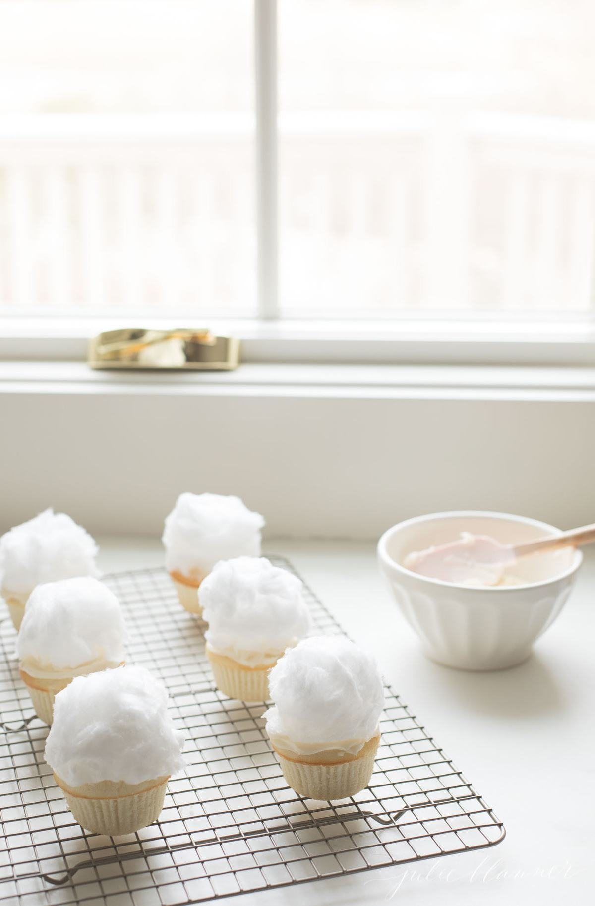 white Easter cupcakes topped with cotton candy to make bunny tails