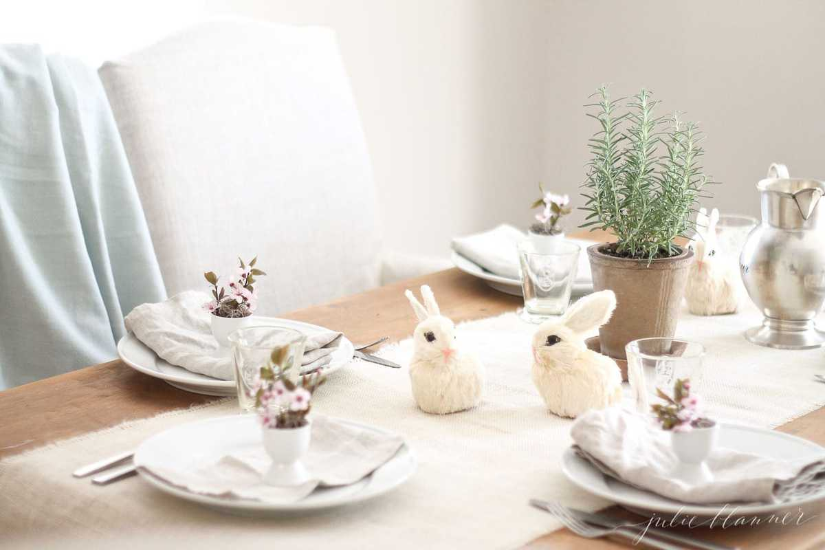 easter decorating ideas on a dining room table filled with egg cups and tiny straw bunnies.