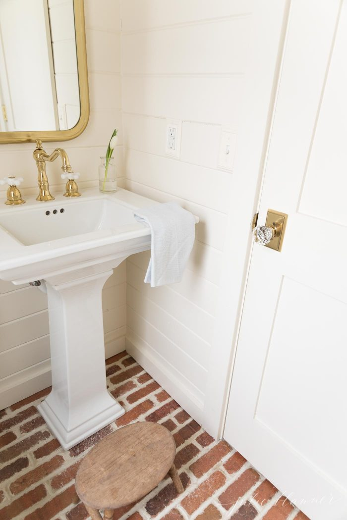 bathroom with pedestal sink brick floors and shiplap