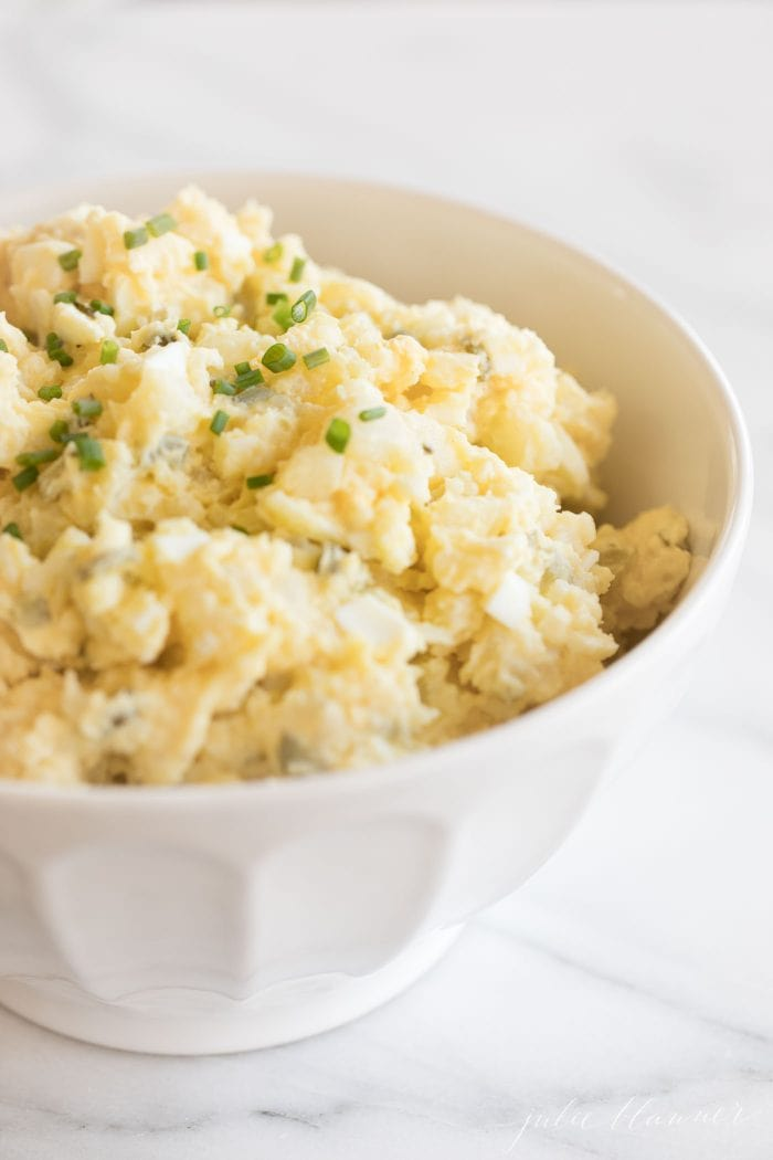 homamade potato salad with eggs in a white bowl