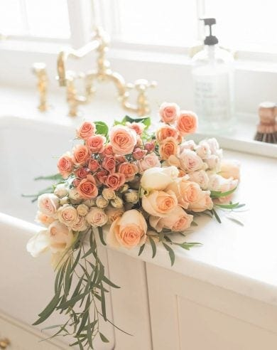 peach flowers in apron front sink