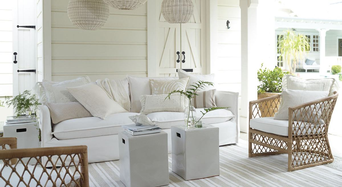 A beachy white room with a white sofa full of mismatched ivory pillow covers.
