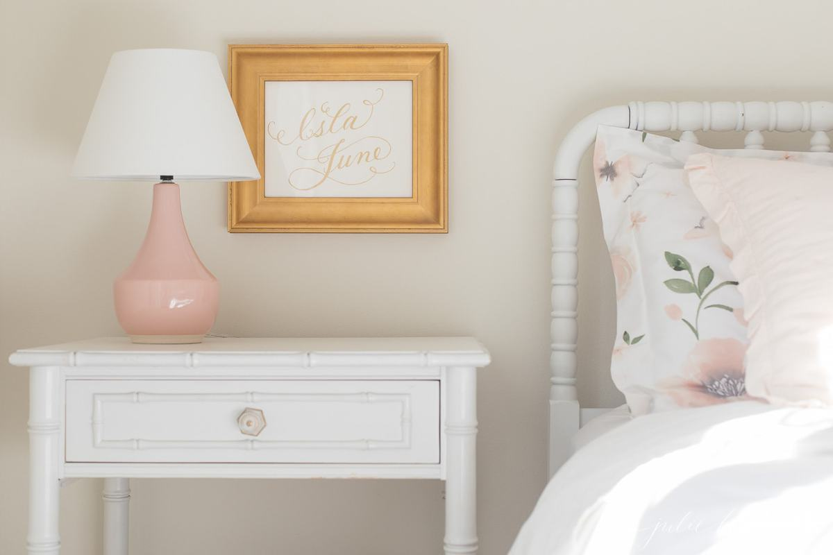 A white girl's bedroom with a pink lamp on a bedside table.
