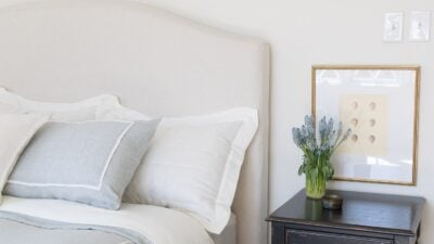 A white bedroom with an upholstered headboard and black nightstand, antique egg printable art over the nightstand.