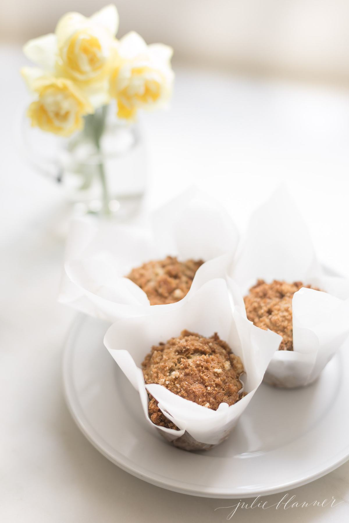 3 banana muffins on a plate with yellow flowers