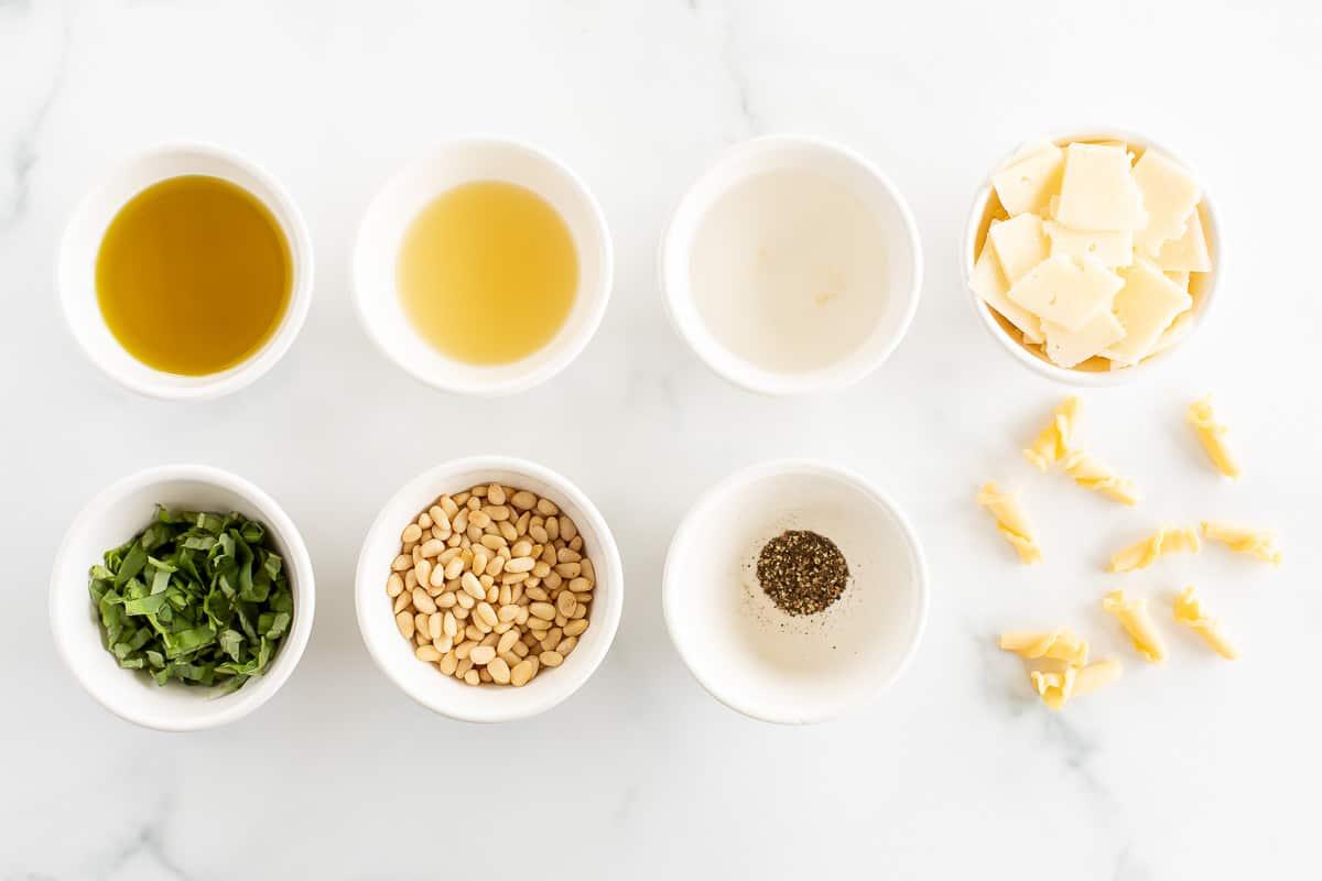 ingredients to make summer pasta salad in white bowls