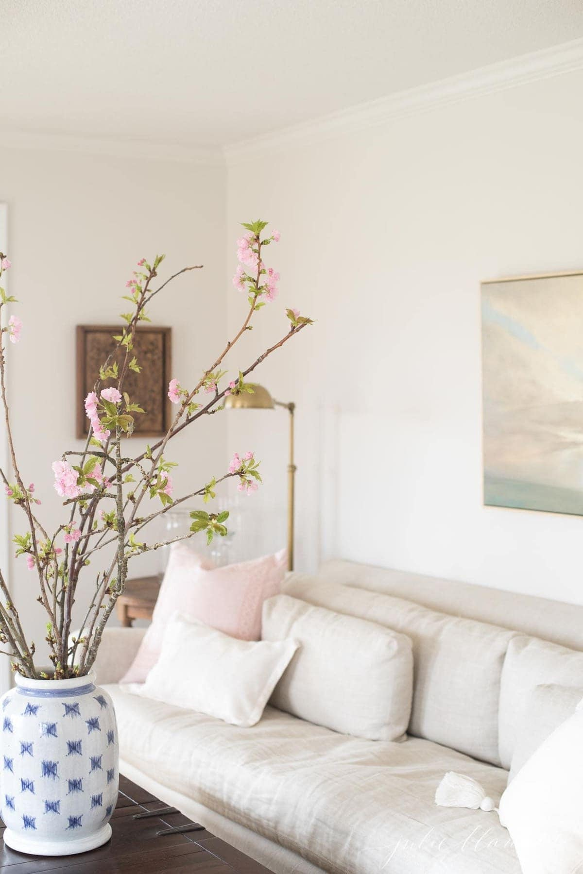 A neutral living room with a linen sofa and tall pink branches in a blue and white vase.