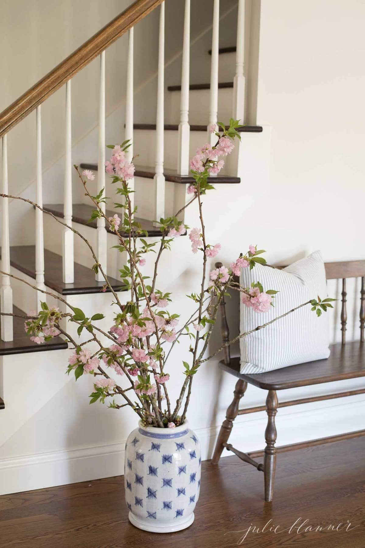 cherry blossom branches in blue and white patterned vase