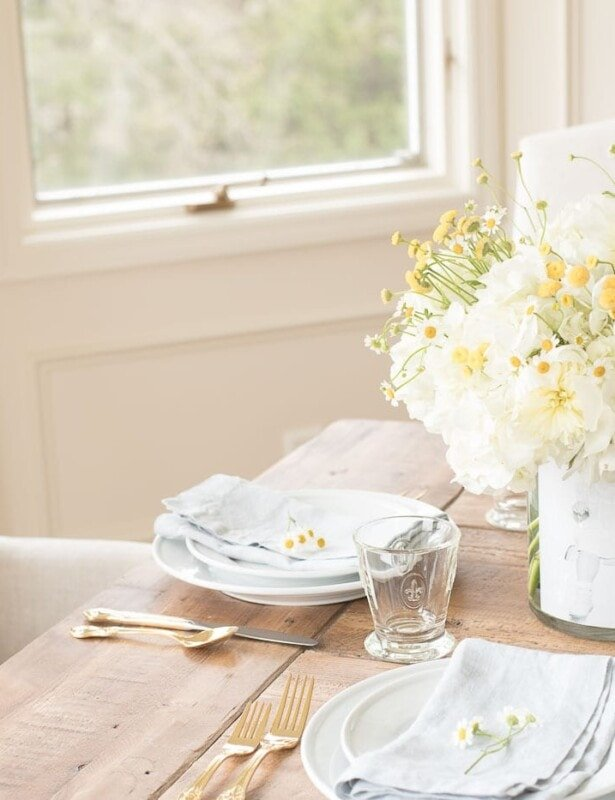 A mother's day decor idea of a DIY photo vase filled with flowers on a table set for brunch.