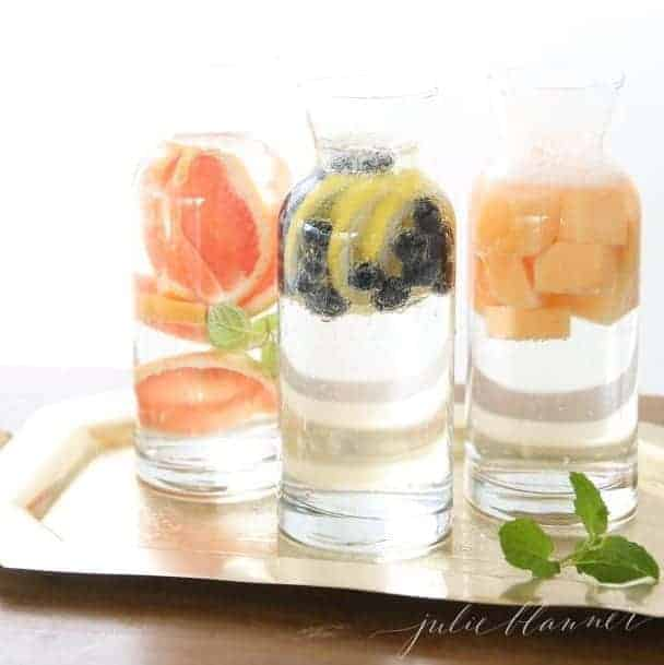 Three clear glass carafes full of fruit infused water.
