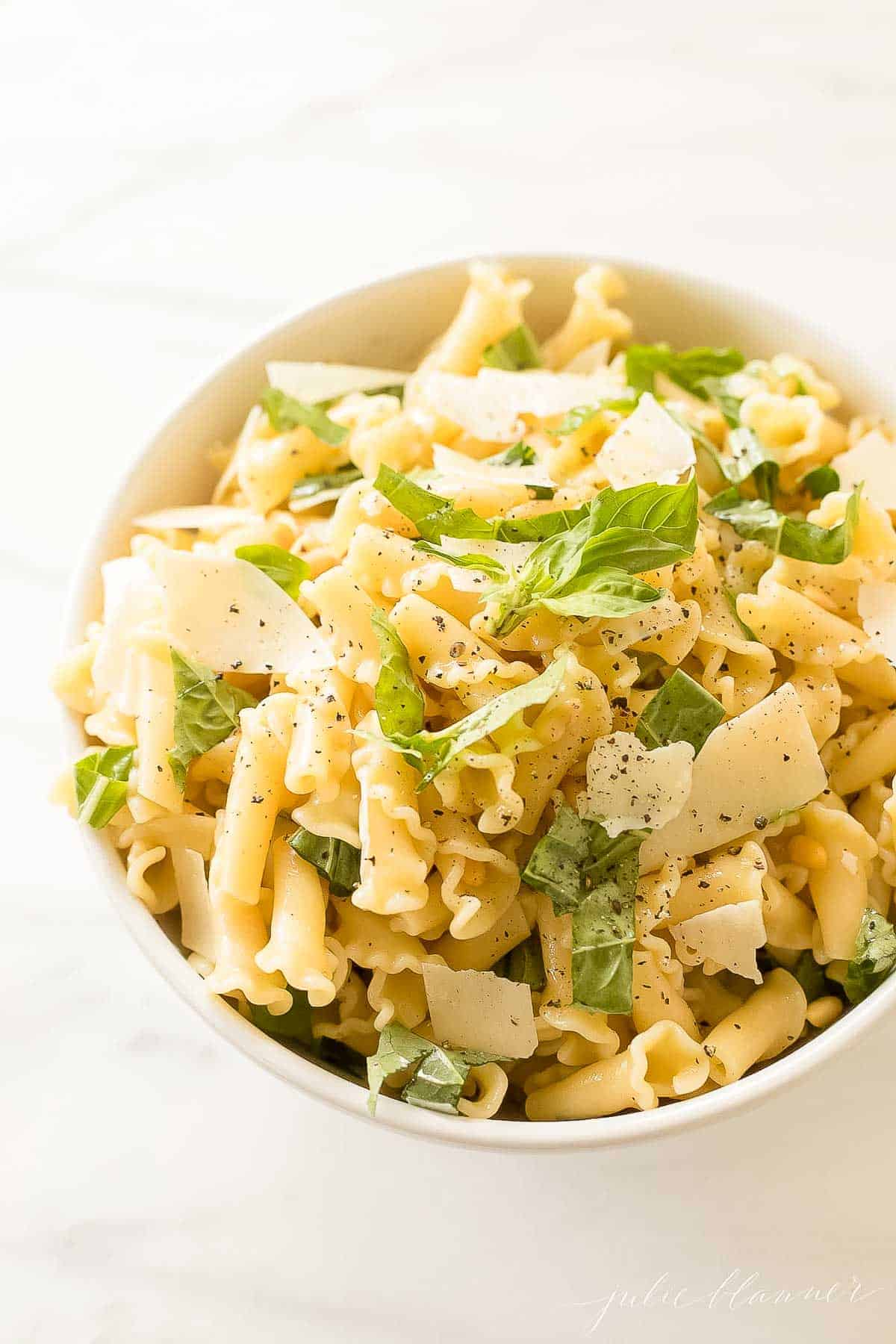 pasta topped with parmesan and basil in white bowl