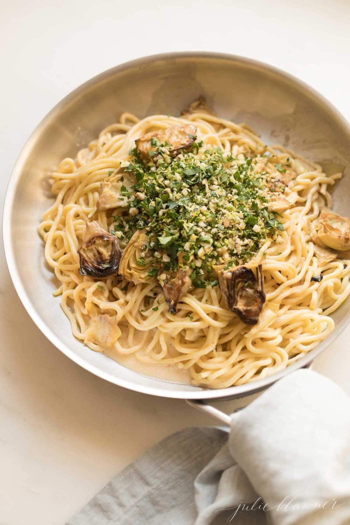 lemon cream sauce over spaghetti with gremolata in pan wrapped with linen